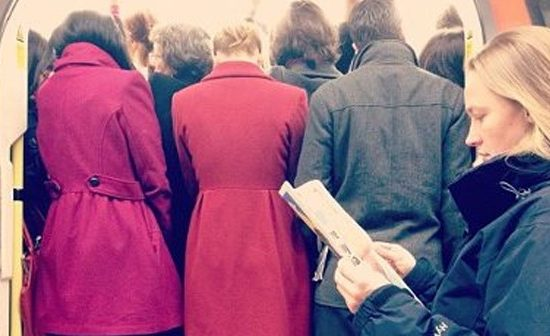 A wall of people on the tube during peak hour and a lady reading her guidebook