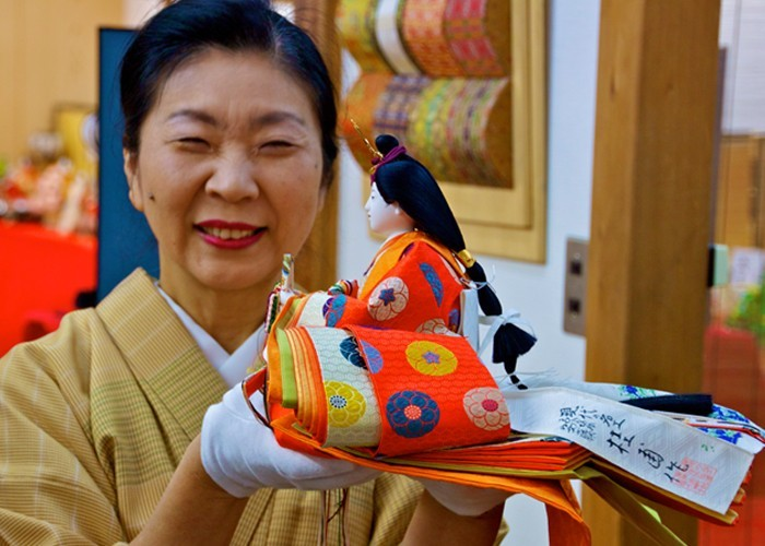 Mrs Ando smiles whilst holding an Empress doll in Kyoto, Japan