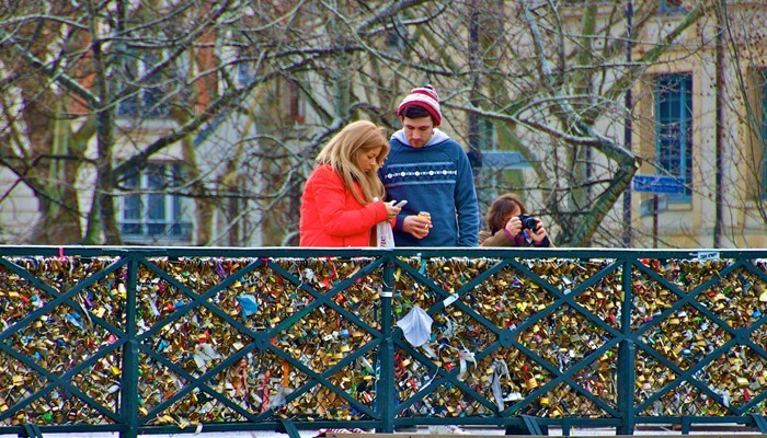 Love locks and a couple fixing a lock on Pont de l'Archevêché - Paris, France
